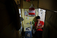 "King, a 18-year old bartender smokes his cigarette in a wooden box he uses as living space early October 9, 2012 in Hong Kong. In Hong Kong's middle-class residential area, short distance from its shopping and financial districts, 24 people live in ""coffin homes"" packed in a single apartment of little over 50 square meters. Its residents pay monthly 1450 Hong Kong dollars (around 180 USD) for their living space built of wooden panels of 2 meters by 70 cm. To maximize income from the rent in central Hong Kong, landlords build such coffin homes, nicknamed because of their resemblance to real coffins. Space has always been at a premium in Hong Kong where developers plant high-rises on every available inch.   REUTERS/Damir Sagolj (CHINA)"