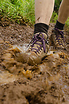 Hiking boots walking along muddy Kuilau Ridge Trail, Lihue-Koloa Forest Reserve, Kauai, Hawaii