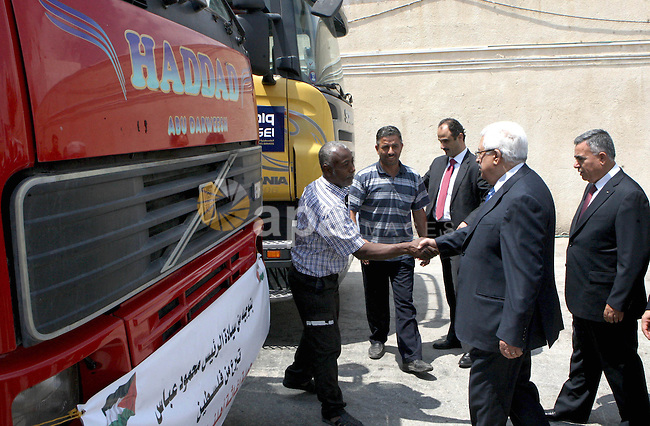 Palestinian President Mahmoud Abbas, os accompanied by other officials as he waves to a convoy of trucks carrying food and medical supplies, which reportedly were provided by the Palestinian people, leaving Ramallah bound for Syria, in Ramallah, West Bank, 05 August 2012. The convoy of 17 trucks started for an aid tour to help the Syrian people and was given a farewell by Palestinian President Mahmoud Abbas. Photo by Thaer Ganaim