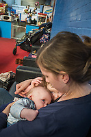 A mother tandem feeds her 2.5 year old daughter and her 5 month old son at a play centre.<br /> <br /> Hampshire, England, UK<br /> 21/03/2016<br /> <br /> &copy; Paul Carter / wdiip.co.uk