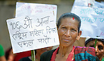 """A woman holds a sign during a march celebrating International Women's Day on March 8, 2016, in Dhawa, a village in the Gorkha District of Nepal. The sign reads, """"Let's make the 106th Women's Day a success."""""""