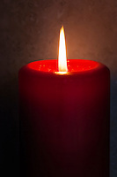 The flame rises from a red candle against a textured background.