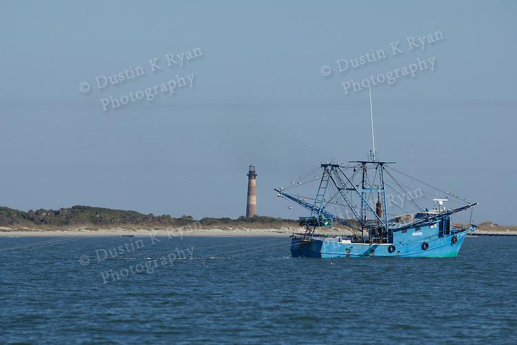 Shrimp boat off folly beach on the Atlantic Ocean South Carolina Blue Morris Island Lighthouse