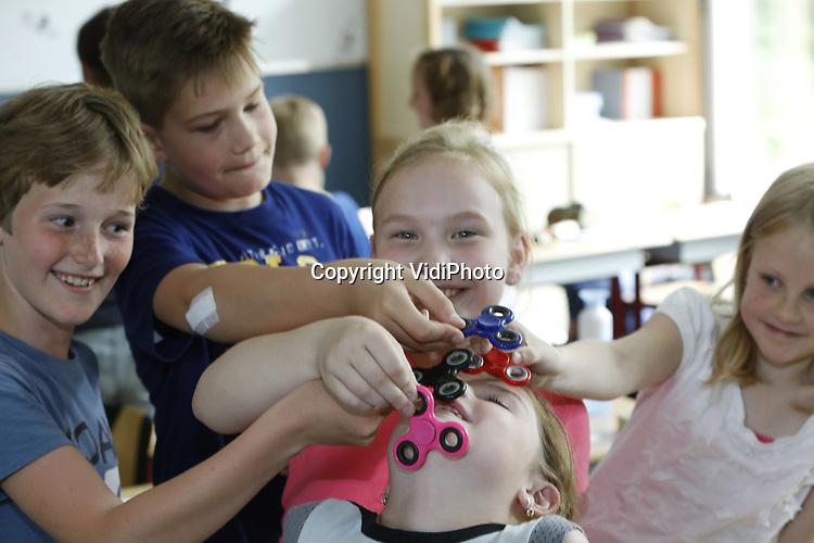 Foto: VidiPhoto<br /> <br /> VEENENDAAL - Leerlingen van de Johannes Calvijnschool in Veenendaal tonen donderdag in de klas hun kunsten met de nieuwste rage van dit moment: de Fidget. Dat is een soort plastic propellertje dat minutenlang kan draaien op vinger, voorhoofd of -bij handige kinderen- andere lichaamsdelen. De kunst is bijvoorbeeld om de draaiende wieltjes al draaiend door te geven aan elkaar. De vraag naar het speeltuig is zo groot dat de meeste speelgoedwinkels inmiddels &quot;nee&quot; moeten verkopen. Sinds er maandag filmpjes op YouTube verschenen met deze nieuwste gadget, zijn de Fidget spinners niet meer aan te slepen. Bij importeur Johntoy in Waddinxveen rijden winkeliers uit zelfs Belgi&euml; en Duitsland af en aan om de handspinner in te slaan. De verwachting dat importeurs de komende weken miljoenen Fidgets op de markt zullen brengen. Bijkomend voordeel voor kinderen met zowel een lage als hoge zintuigelijke prikkelverwerking is dat ze dan beter opletten in de klas. Voorlopig worden de speeltjes echter in de klas geweerd.