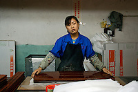 Worker in packing department of Hong Qi wood floor factory, a private firm which produces floor boards for the booming domestic market and for export around the world, using imported wood.