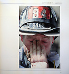 A New York City firefighter wipes his eyes during a break from working in the debris of the World Trade Center the day after it collapsed on September 11, 2001.