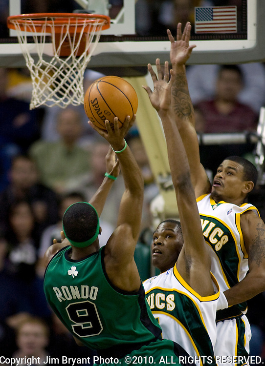 Boston Celtics' Rajon Rondo (L) goes up for a shot against defending Seattle SuperSonics' Kevin Durant (C) and Earl Watson (R)  during the half at the Key Arena in Seattle on December 27, 2007.  Jim Bryant Photo. ©2010. All Rights Reserved.