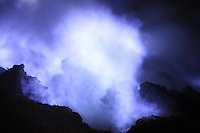 Kawah Ijen Volcano, Java, Indonesia showing blue gases of burning sulfur.
