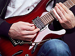 Closeup of man hands playing red electric guitar with a slide
