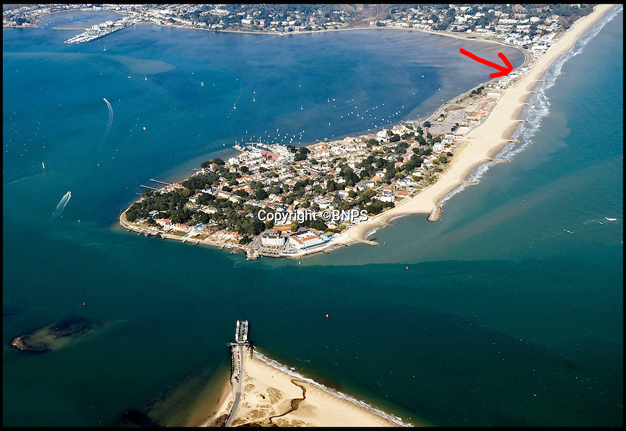 BNPS.co.uk (01202 558833)<br /> Pic: PeterWillows/BNPS<br /> <br /> Sandbanks peninsula in Poole, Dorset.  Arrow shows location of plot on Banks Road.<br /> <br /> A humble holiday home a family bought for just &pound;1,000 almost a century ago on the exclusive enclave of Sandbanks has turned into a luxury property now worth &pound;5 million.<br /> <br /> The bungalow was bought new by Dr Edward Andreae in the 1920s when the practice of building on the sandy Dorset peninsula was questioned because of perceived issues over stability.<br /> <br /> Over the last seven decades the bolthole has been passed down through the generations of the same family until it fell into a state if disrepair.<br /> <br /> In 2011 Dr Andreae's great-grandson, Tim Baldwin, and his father Jonathan, made the drastic decision to demolish the 90 year old building and erect a new one in its place.<br /> <br /> They spent 580,000 pounds creating a luxurious beach escape on the 'Millionaires' Row' in Poole Harbour.<br /> <br /> The plot is now home to a sprawling seven bedroom, five bathroom property which experts believe to be worth around five million pounds - 5,000 times it's original purchase price.