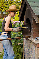 A young woman in a cowboy hat removes a pan of baked custard from an outdoor brick, wood-fired oven at Dufferin Grove park in Toronto.
