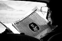 A guide reads a newspaper while traveling through the Gobi Desert.