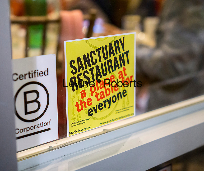 """A sign in the window of the Green Table restaurant in Chelsea in New York announces that it is a """"sanctuary restaurant"""" protecting immigrant rights, seen on Thursday, January 26, 2017. The """"sanctuary restaurant"""" movement is an effort to protect workers in the restaurant industry which employees many immigrants. (© Richard B. Levine)"""