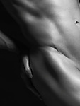 Young nude man with fit body, closeup of hip isolated on black background artistic black and white photo