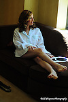 Bride relaxes before her ceremony on a  couch by window in her suite at the Essex House...