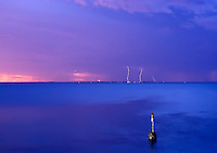 Lightning over Rottnest Island lights up the evening sky and the famous Cottesloe Pylon.
