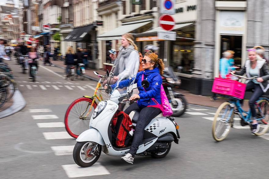 Nederland, Amsterdam, 30 mei 2015<br /> Snorscooter in het centrum van de stad.  Scooters stoten veel fijn stof uit en zijn enorm ongezond voor de stadsbewoners. De luchtkwaliteit wordt ernstig aangetast door scooters en bromfietsen of snorfietsn. <br />  <br /> Foto: Michiel Wijnbergh