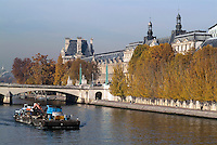 Barge carrying machinery travelling down the Seine, Paris, France.