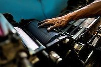 A Colombian master printer works on the letterpress machine in the print shop in Cali, Colombia, 1 June 2012. Letterpress printing, invented by Johannes Gutenberg in the 15th century, remained the primary way to print and distribute information until the second half of the 20th century. The process of letterpress printing consists of composing movable types into the bed of a press, inking it, and pressing paper against it to create an impression. Nowadays, due to the offset printing expansion, there are few commercial print shops in the world keeping this traditional craftsmanship alive.