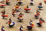Cloaked in long, colorful costumes, a troupe of Bhutanese dancers resemble spinning tops as they celebrate at a Buddhist festival or tsechu in the courtyard of Paro Dzong.