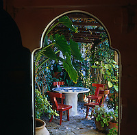 A round pedestal table with a mosaic tiled top is surrounded by a group of chairs designed by John Stefanidis under a pergola in the garden