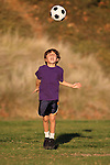 Boy playing with soccer ball in early evening sunlight with Fall or Autumn foliage behind him.