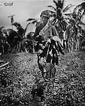 "Marine PFC Fred Voight and his Devil Dog ""Lucky"" return to the dog contingent bivouac after several active patrols on the front lines on Guam. Lucky, a Doberman-Pinscher, formerly of Long Island, poited to a number of Japanese fighters during the day whom his partner promptly eliminated."