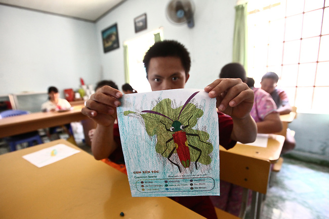 A boy holds a page that he has colored at a day care center for children affected by dioxin exposure in Da Nang, Vietnam. The Da Nang Association of Victims of Agent Orange/Dioxin says that more than 1,400 children around the city suffer from mental and physical disabilities because of dioxin exposure, a legacy of the U.S. military's use of Agent Orange and other herbicides during the Vietnam War more than 40 years ago. About 200 children attend three centers operated by the group, giving their parents the opportunity to work away from home, often for the first time. The Vietnam Red Cross estimates that 3 million Vietnamese suffer from illnesses related to dioxin exposure, including at least 150,000 people born with severe birth defects since the end of the war. The U.S. government is paying to clean up dioxin-contaminated soil at the Da Nang airport, which served as a major U.S. base during the conflict. But the U.S. government still denies that dioxin is to blame for widespread health problems in Vietnam and has never provided any money specifically to help the country's Agent Orange victims. May 28, 2012.