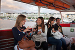 Women laughing and looking at photos on a cell phone while riding the water taxi on Lake Geneva in Geneva, Switzerland