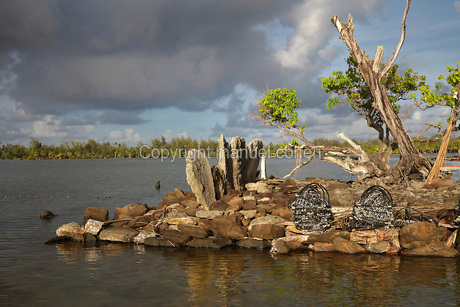Marae Orohaa, a ruined stone courtyard with platform and standing stones, built by a Polynesian civilisation and used as a ceremonial and religious site, with a pile of fishing nets, on the banks of Lake Fauna Nui or Maeva Lake, at the archaeological site at Maeva village, on Huahine-Nui on the island of Huahine, in the Leeward Islands, part of the Society Islands, in French Polynesia. The marae were used for worshipping ancestors and gods, and offerings were made here. The marae are thought to date from 13th - 15th centuries. Maeva is thought to be an abandoned royal settlement, with many megalithic structures including marae, houses, agricultural structures, stone fish traps and fortification walls. Picture by Manuel Cohen