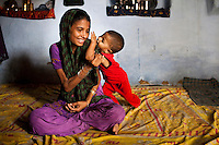 Sadma Khan, 19, plays with her 18 month old son in her mother's one-room house which she shares with 5 other family members in a slum area of Tonk, Rajasthan, India, on 19th June 2012. She was married at 17 years old to Waseem Khan, also underaged at the time of their wedding. The couple have an 18 month old baby and Sadma is now 3 months pregnant with her 2nd child and plans to use contraceptives after this pregnancy. She lives with her mother since Waseem works in another district and she can't take care of her children on her own. Photo by Suzanne Lee for Save The Children UK