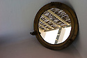Santorini, Greece. 05.05.2014. An abstract image of the reflection of a bamboo roof to a balcony at Hotel Notos in a round, porthole mirror, Vlychada, Santorini, Greece. Photograph © Jane Hobson.