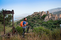 Vathia, Mani, Peloponnesos, Greece, May 2013. Mountaineer Thanos, who is working on the restauration of some ancient Mani Tower houses in Vathia, guides us over the path past the temple of Poseidon down to the lighthouse at Cape Tainaron. The sizeable building, which once housed a keeper and his family, is deserted and its operation has been<br /> automated. At 36.4&deg; latitude, you are further south than Tunis and Algiers, and only marginally further north than Tarifa, mainland Europe&rsquo;s southernmost point. Tankers ply past in both directions with a faint rumble.<br />  of The Peloponnese peninsula offers beautiful hikes along the bays and capes of the Mani and Monemvasia and the interior Taygetos. Venture inland, away from the crowds, and there are some surprises in store: snow-capped mountains, limestone gorges, shady rivers, crumbling castles, tower-villages, fir forests, frescoed chapels, and solated monasteries. Ancient mountain villages interrupt the olive groves that line the rugged coastline that is surrounded by deep blue and turquoise waters of the Mediterranean.  Photo by Frits Meyst/Adventure4ever.com