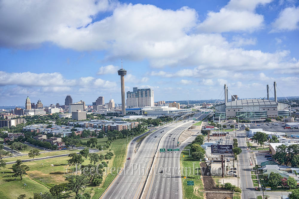 We took this San Antonio skyline view from the south side so it would show downtown buildings along with the Hemisphere and Alamo Dome. This scene includes the San Antonio Skyline with the Tower of Americas and behind it is the new Henry B Gonzales convention with the Hemisphere which stands 750 ft along with the Grand Hyatt, Marriott, the Alamo Dome, UT SA, Tower Life building, Bank of American Plaza and many others.  Most of the hotels and high-rise structures are center around the River Walk which is an iconic part of the SA tourist industry. It looks like we were took this over the highway, but it was not taken there it was  an area that gave that perspective.