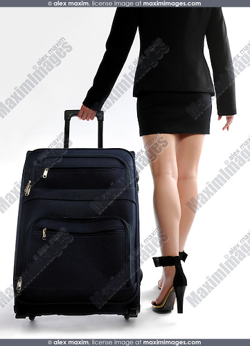 Businesswoman with sexy long legs on high heels wheeling a big trunk walking away