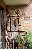 Insekten-Hotel, Insektenhotel, verschiedene Nisthilfen für Hymenopteren auf einem Balkon, Baumscheiben mit Bohrlöchern, Lehm, hohle Pflanzenstängel, Todholz bieten Nistmöglichkeiten für solitäre Wildbienen und Wespen