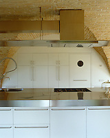 The modern Boffi kitchen cabinets are recessed seamlessly into the arches which support the vaulted ceiling in the kitchen