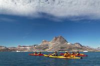 Sea kayakers paddling on Sammileq Fjord, Ammassalik Island, East Greenland