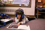Oakland CA Kindergarten student listening to book on tape in class (prereading) MR