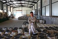 Monsieur Chiang Ping devant ses futs de miels rares dans le Yunnan.///Mister Chiang Ping in front of his rare honey jars.