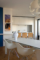 The contemporary kitchen/dining area is furnished with a set of Eames chairs and designer lighting