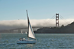 Golden Gate Bridge in San Francisco, California with fog and sailboats