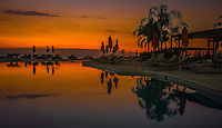Fine Art Photograph. Sunset on Banderas Bay, Puerto, Vallarta, Mexico. Grand Venitian pool. Silhouettes and pool reflections from the golden rays of the setting sun.