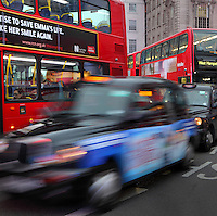 London traffic atmosphere, a cab pulls away and opens the way to the vehicules behind, on the adjacent line a red London bus is stopped, UK. Picture by Manuel Cohen
