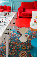 The sitting room combines as games room, its turquoise-painted panelled walls reflecting the colours of the Azerbaijan rug on the red-painted wooden floor
