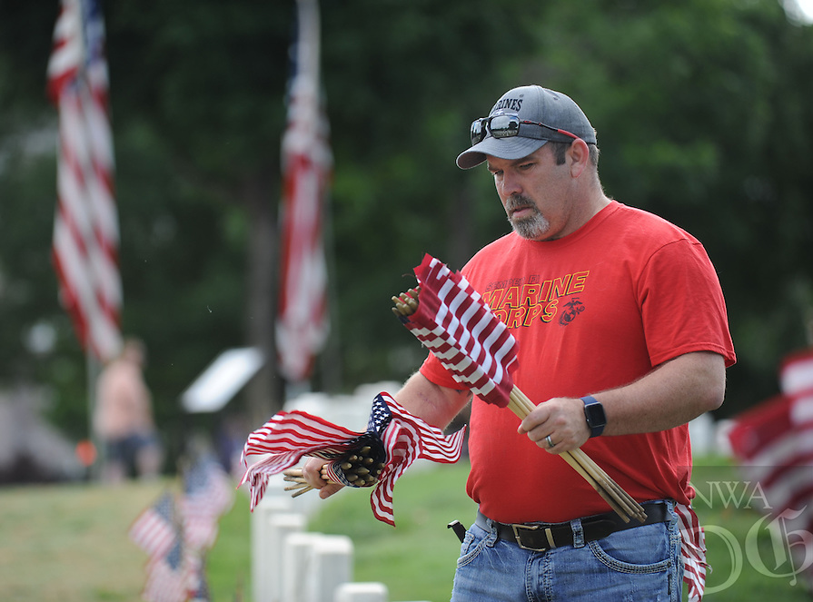 NWA Democrat-Gazette/ANDY SHUPE<br /> Eric Wood of Bentonville, a veteran of the U.S. Marine Corps, places flags Saturday, May 28, 2016, along a row of grave markers at the Fayetteville National Cemetery. Volunteers placed flags in front of the approximately 8,700 grave markers at the facility ahead of the Memorial Day holiday. A service is planned for 10 a.m. Monday at the cemetery featuring Col. Bobbi Doorenbos, commander of Arkansas Air National Guard&rsquo;s 188th Wing.