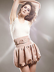 High fashion studio photo of a beautiful woman wearing a beige balloon skirt. The photo is not model released, however the model release can be acquired from the modeling agency if necessary. Agency's fees may apply depending on the usage.