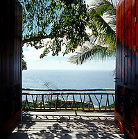 Wooden doors open onto a balcony with an uninterrupted view of the Pacific ocean