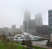 Luxury Yacht with skyscrapers in the mist, Canary Wharf, West India Docks on the Isle of Dogs, Borough of Tower Hamlets, East London, UK. Picture by Manuel Cohen
