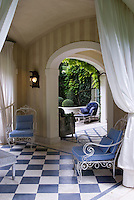 The loggia is furnished with wrought iron garden chairs and wicker tables and features a black and white tiled floor